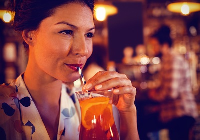 Young woman having cocktail drink in pub